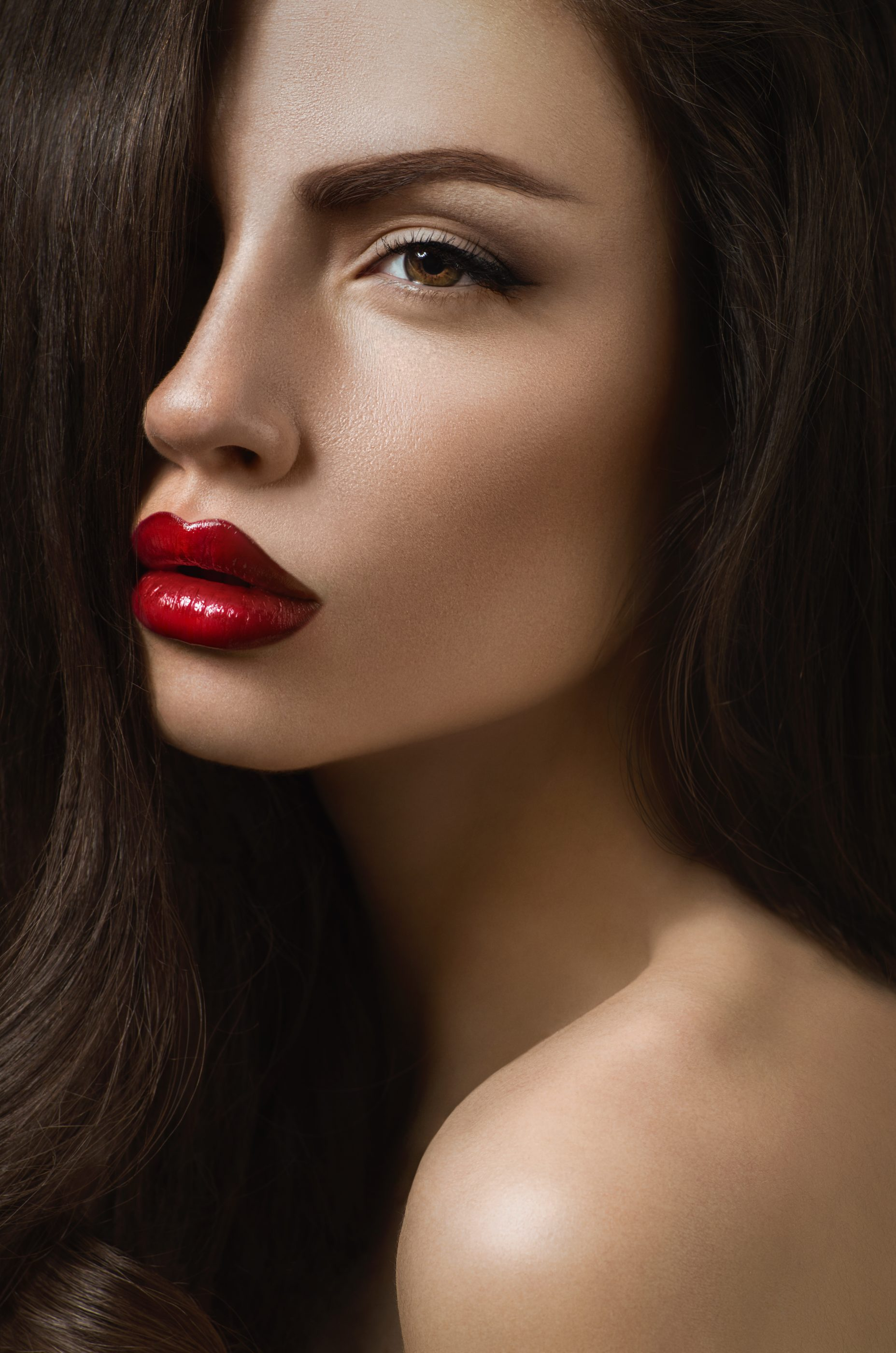 Posh brunette woman with sexy red lips and perfect pure skin